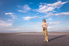 Γυναίκα με τη κάμερα που στέκεται και που χαμογελά κοντά στην παραλία Στοκ Εικόνες