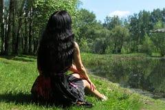 Γυναίκα με τη μαύρη συνεδρίαση τρίχας πίσω στη φύση Στοκ εικόνα με δικαίωμα ελεύθερης χρήσης