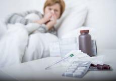γυναίκα με τη μύτη φτερνίσματος που φυσά στον ιστό στο κρεβάτι που υφίσταται τα κρύα συμπτώματα ιών γρίπης που έχουν τα χάπια ταμ Στοκ Φωτογραφίες