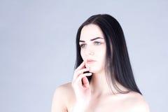 Γυναίκα με τη σκοτεινή τρίχα σχετικά με το μάγουλο με το χέρι ανασκόπησης ομορφιάς μπλε έννοιας εμπορευματοκιβωτίων καλλυντικός β Στοκ φωτογραφίες με δικαίωμα ελεύθερης χρήσης