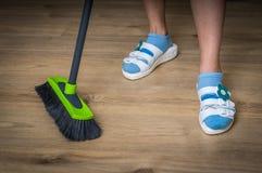 Γυναίκα με τη σκούπα που σκουπίζει το ξύλινο φυλλόμορφο πάτωμα Στοκ φωτογραφίες με δικαίωμα ελεύθερης χρήσης
