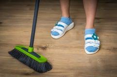 Γυναίκα με τη σκούπα που σκουπίζει το ξύλινο φυλλόμορφο πάτωμα Στοκ Φωτογραφία