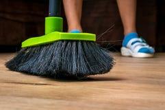 Γυναίκα με τη σκούπα που σκουπίζει το ξύλινο φυλλόμορφο πάτωμα Στοκ Εικόνες