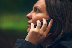 Γυναίκα με τη σοβαρή έκφραση προσώπου που μιλά στο τηλέφωνο στο πάρκο Στοκ φωτογραφία με δικαίωμα ελεύθερης χρήσης