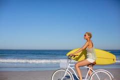 Γυναίκα με τη συνεδρίαση ιστιοσανίδων στο ποδήλατο στην παραλία στην ηλιοφάνεια στοκ φωτογραφία με δικαίωμα ελεύθερης χρήσης