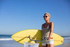 Γυναίκα με τη συνεδρίαση ιστιοσανίδων στο ποδήλατο στην παραλία στην ηλιοφάνεια στοκ εικόνες