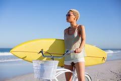 Γυναίκα με τη συνεδρίαση ιστιοσανίδων στο ποδήλατο στην παραλία στην ηλιοφάνεια στοκ εικόνα