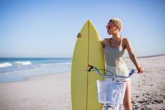 Γυναίκα με τη συνεδρίαση ιστιοσανίδων στο ποδήλατο στην παραλία στην ηλιοφάνεια στοκ φωτογραφίες με δικαίωμα ελεύθερης χρήσης