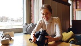 Γυναίκα με τη συνεδρίαση καμερών στον καφέ απόθεμα βίντεο
