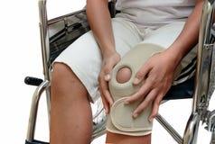 Γυναίκα με τη συνεδρίαση πόνου γονάτων στην αναπηρική καρέκλα Στοκ Εικόνα