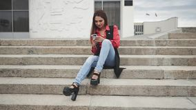 Γυναίκα με τη συνεδρίαση smartphone στα σκαλοπάτια στην πόλη απόθεμα βίντεο