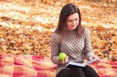 Γυναίκα με τη συνεδρίαση βιβλίων και μήλων σε μια κουβέρτα Στοκ Φωτογραφία