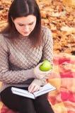 Γυναίκα με τη συνεδρίαση βιβλίων και μήλων σε μια κουβέρτα Στοκ Φωτογραφίες