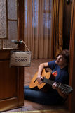 Γυναίκα με τη συνεδρίαση κιθάρων στο πάτωμα στον καφέ στοκ εικόνα με δικαίωμα ελεύθερης χρήσης