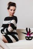 Γυναίκα με τη συνεδρίαση μασκών καρναβαλιού στον καναπέ Στοκ εικόνες με δικαίωμα ελεύθερης χρήσης