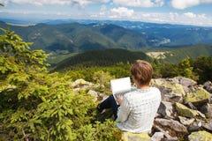 Γυναίκα με τη συνεδρίαση lap-top σε μια πέτρα Στοκ Εικόνες