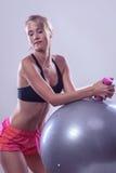 Γυναίκα με τη σφαίρα γυμναστικής και αλτήρας που κάνει την άσκηση Στοκ Εικόνες