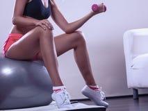 Γυναίκα με τη σφαίρα γυμναστικής και αλτήρας που κάνει την άσκηση Στοκ Φωτογραφία