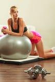 Γυναίκα με τη σφαίρα γυμναστικής και αλτήρας που κάνει την άσκηση Στοκ εικόνα με δικαίωμα ελεύθερης χρήσης