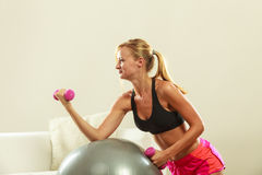 Γυναίκα με τη σφαίρα γυμναστικής και αλτήρας που κάνει την άσκηση Στοκ Φωτογραφίες