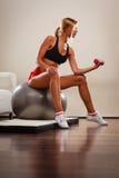 Γυναίκα με τη σφαίρα γυμναστικής και αλτήρας που κάνει την άσκηση Στοκ φωτογραφία με δικαίωμα ελεύθερης χρήσης