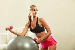 Γυναίκα με τη σφαίρα γυμναστικής και αλτήρας που κάνει την άσκηση Στοκ φωτογραφίες με δικαίωμα ελεύθερης χρήσης