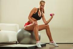 Γυναίκα με τη σφαίρα γυμναστικής και αλτήρας που κάνει την άσκηση Στοκ εικόνες με δικαίωμα ελεύθερης χρήσης