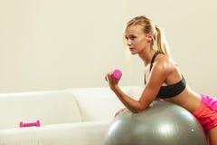 Γυναίκα με τη σφαίρα γυμναστικής και αλτήρας που κάνει την άσκηση Στοκ Εικόνα
