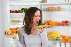 Γυναίκα με τη Apple που τρώει doughnut Στοκ Εικόνες