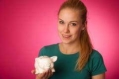 Γυναίκα με τη piggy τράπεζα στα χέρια που διεγείρονται στο χρηματοκιβώτιο εκτός από την αποταμίευση Στοκ Φωτογραφίες
