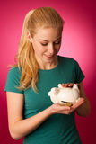 Γυναίκα με τη piggy τράπεζα στα χέρια που διεγείρονται στο χρηματοκιβώτιο εκτός από την αποταμίευση Στοκ Φωτογραφία