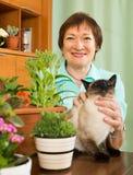Γυναίκα με τις εγκαταστάσεις γατών και λουλουδιών Στοκ Φωτογραφίες