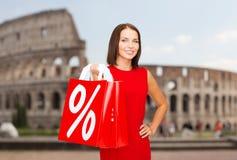 Γυναίκα με τις κόκκινες τσάντες αγορών πέρα από το coliseum Στοκ Εικόνα