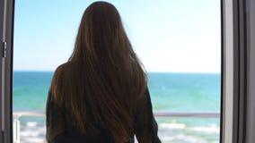 Γυναίκα με τις μακρυμάλλεις ανοίγοντας πόρτες μπαλκονιών και εξέταση έξω τη θάλασσα Απολαμβάνοντας τη θέα θάλασσας έξω Σε αργή κί φιλμ μικρού μήκους