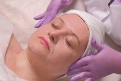 Γυναίκα με τις προσοχές ιδιαίτερες σε μια καλλυντική διαδικασία σε ένα σαλόνι ομορφιάς Τα χέρια ενός cosmetologist στα ιώδη γάντι στοκ φωτογραφίες με δικαίωμα ελεύθερης χρήσης