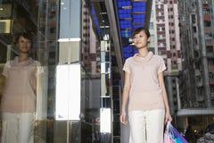 Γυναίκα με τις τσάντες αγορών που εξετάζει την επίδειξη παραθύρων Στοκ Φωτογραφία