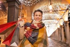 Γυναίκα με τις τσάντες αγορών που στέκονται κάτω από το φως Χριστουγέννων, Βενετία Στοκ εικόνες με δικαίωμα ελεύθερης χρήσης