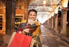 Γυναίκα με τις τσάντες αγορών που στέκονται κάτω από το φως Χριστουγέννων, Βενετία Στοκ Φωτογραφία