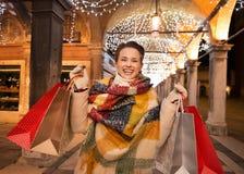 Γυναίκα με τις τσάντες αγορών που στέκονται κάτω από το φως Χριστουγέννων, Βενετία Στοκ Φωτογραφίες
