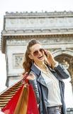Γυναίκα με τις τσάντες αγορών στο Παρίσι, Γαλλία που χρησιμοποιεί το smartphone Στοκ Εικόνες