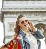 Γυναίκα με τις τσάντες αγορών στο Παρίσι, Γαλλία που χρησιμοποιεί το smartphone Στοκ Φωτογραφία
