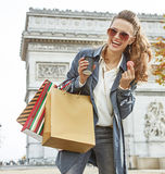 Γυναίκα με τις τσάντες αγορών στο Παρίσι που έχει τον καφέ και macaroon Στοκ Φωτογραφία
