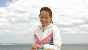 Γυναίκα με τον ιχνηλάτη ικανότητας που τρέχει κατά μήκος της παραλίας απόθεμα βίντεο
