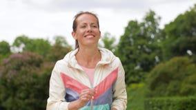 Γυναίκα με τον ιχνηλάτη ικανότητας που τρέχει στο πάρκο απόθεμα βίντεο