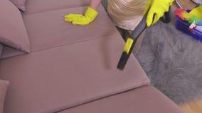 Γυναίκα με τον καθαρισμό ηλεκτρικών σκουπών στις μη διαθέσιμες θέσεις καναπέδων απόθεμα βίντεο