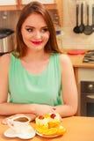 Γυναίκα με τον καφέ και κέικ στην κουζίνα gluttony Στοκ φωτογραφία με δικαίωμα ελεύθερης χρήσης