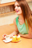 Γυναίκα με τον καφέ και κέικ στην κουζίνα gluttony Στοκ Εικόνες