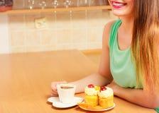 Γυναίκα με τον καφέ και κέικ στην κουζίνα gluttony Στοκ Φωτογραφία