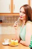 Γυναίκα με τον καφέ που τρώει το κέικ κρέμας gluttony Στοκ Φωτογραφίες