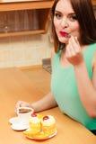 Γυναίκα με τον καφέ που τρώει το κέικ κρέμας gluttony Στοκ Φωτογραφία